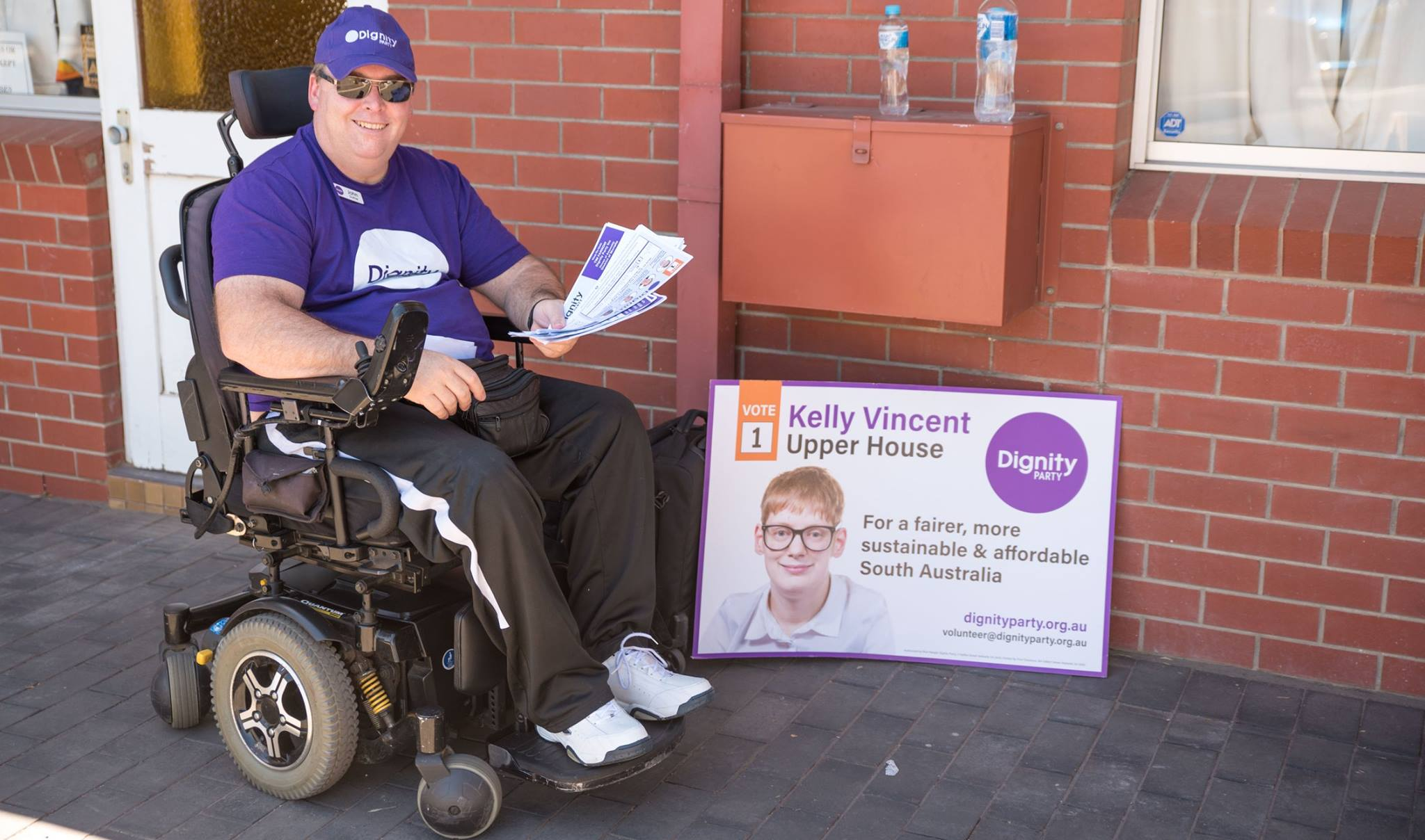 john duthie in a wheelchair looking quite fat and handing out how to vote cards - dignity party campaign